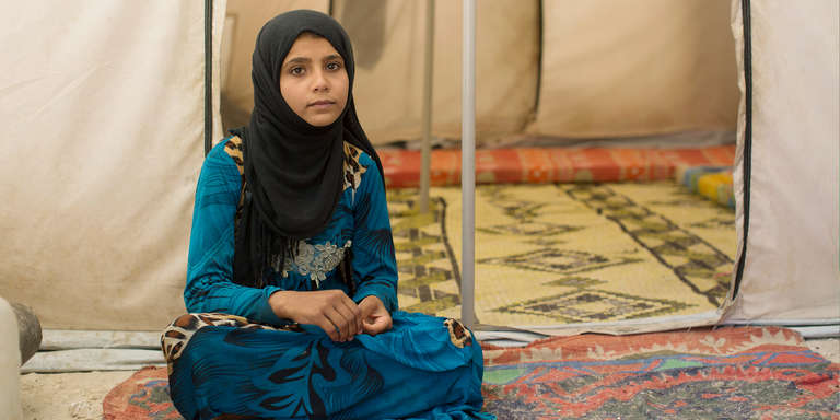 A 13-year-old girl from Raqqa, Syria, sits inside the tent in which she and her family now live, in a camp for people displaced by war. Faridah left Raqqa with her parents and nine siblings three months ago. Photo credit: Sam Tarling / Save the Children, August 2017.