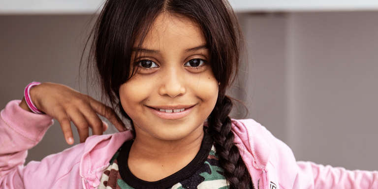 Eight-year-old Johaumi smiles brightly, dressed in a pink sweatshirt and her dark hair in a long braid. Johaumi is a Venezuelan migrant living with her mother and siblings in a dusty border town in northern Colombia. The area is a hotbed of trafficking and brutality and is now home to thousands of Venezuelan migrants who have been driven out of their country by hunger, extreme poverty and violence. They sleep on the street. Photo credit: Sacha Myers / Save the Children, October 2018.