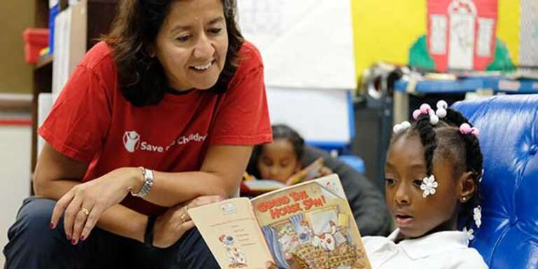 CEO Janti Soeripto wears a Save the Children shirt and looks on as a young girl reads a book.