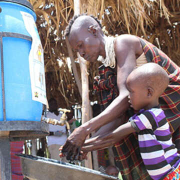 Jacinta, a resident from Central Turkana, washing hands of her child to curb the spread of Covid-19.