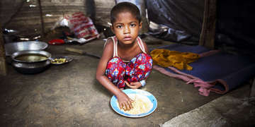 A five-year-old girl crouches on the ground inside her family's makeshift tent, her hand in a plate of meal. The girl and her family fled Myanmar when their village was attacked, and they're now living in a refugee camp in Cox's Bazar, Bangladesh. Save the Children is delivering life-saving interventions such as food, shelter and household supplies. Photo credit: GMB Akash / Panos Pictures / Save the Children, October, 2017.