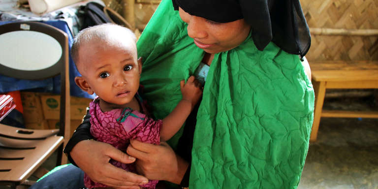 A 1-year-old baby girl clings to her mother at a Save the Children nutrition center in Cox's Bazar, Bangladesh. Rohingya refugees – the mother is waiting to get a dose of Vitamin A for her daughter as part of Nutrition Action week.  Photo credit: Daphnee Cook / Save the Children, July 2018.