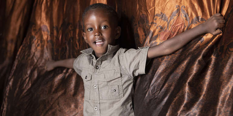 A three-year old boy smiles while standing in his home. In Somalia, where the boy lives, Save the Children is working to protect children and families from the devastating effects of hunger. Photo credit: Kate Stanworth / Save the Children, April 2019.
