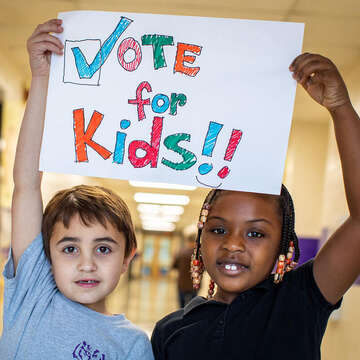 "Two children hold a sign to ""Vote for Kids."""