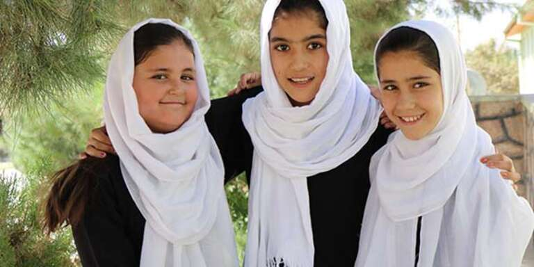 Three girls stand together outside their school in Afghanistan.