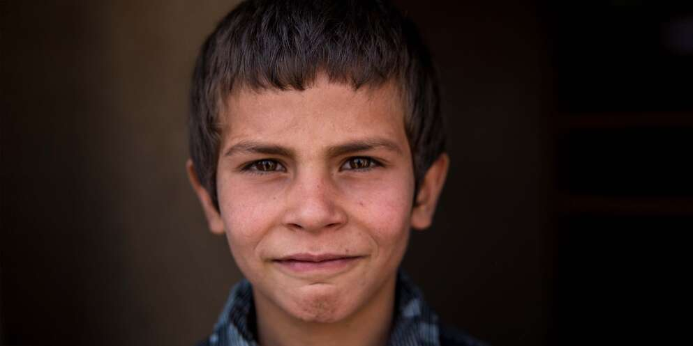 A boy stands quietly against a dark background in Afghanistan.