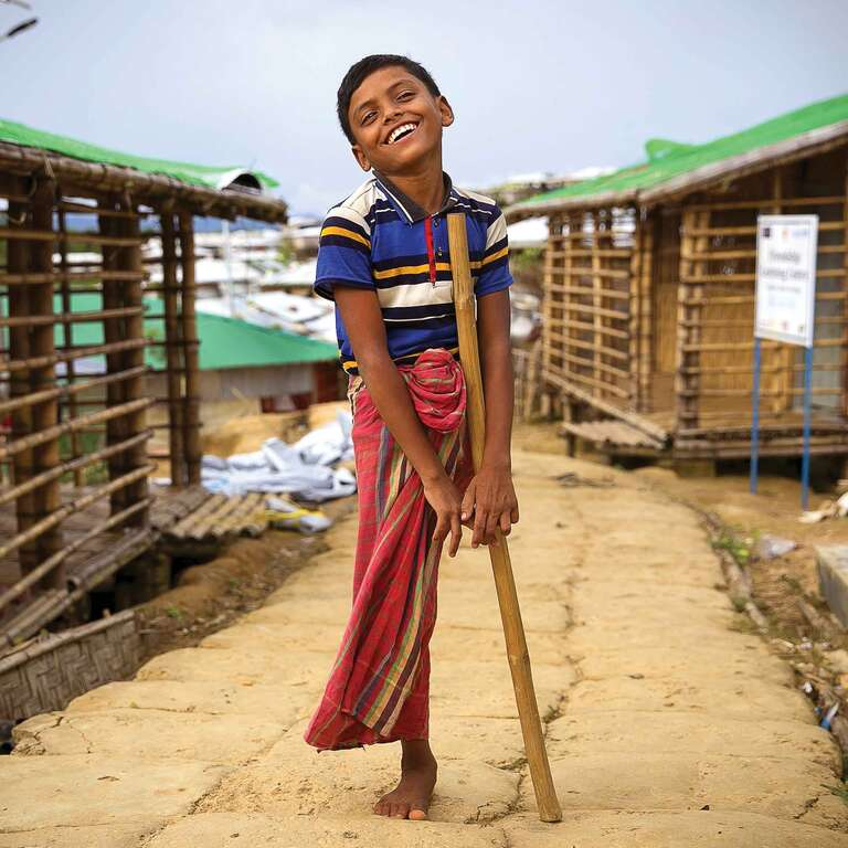 A boy stands and smiles while standing on one leg in Cox's Bazar, Bangladesh.
