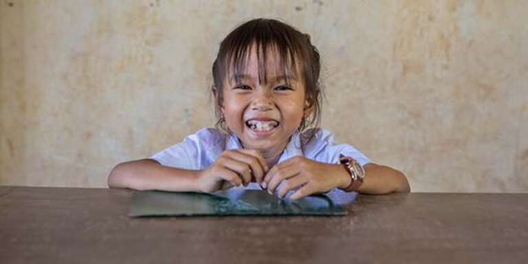A young girl poses with a big smile on her face while sitting at a table in Cambodia.