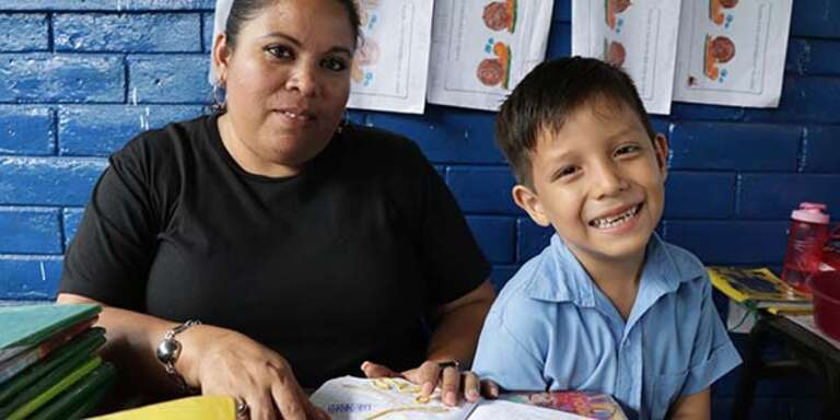 A kindergarten student in El Salvador checks his homework with his teacher.