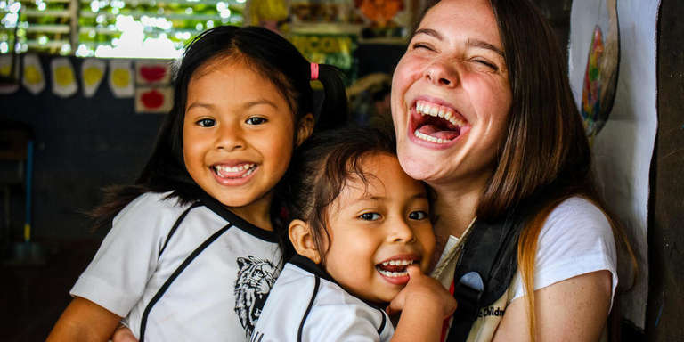 4-year-olds Julisa, left, and Valentina, center, embrace Save the Children staff member Victoria Zeger during a reading club for kindergarden students in the Sonsonate region of El Salvador.. Photo Credit: Save the Children, July 2018