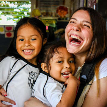 4-year-olds Julisa, left, and Valentina, center, embrace Save the Children staff member Victoria Zeger during a reading club for kindergarden students in the Sonsonate region of El Salvador. Photo Credit: Save the Children, July 2018 Victoria.