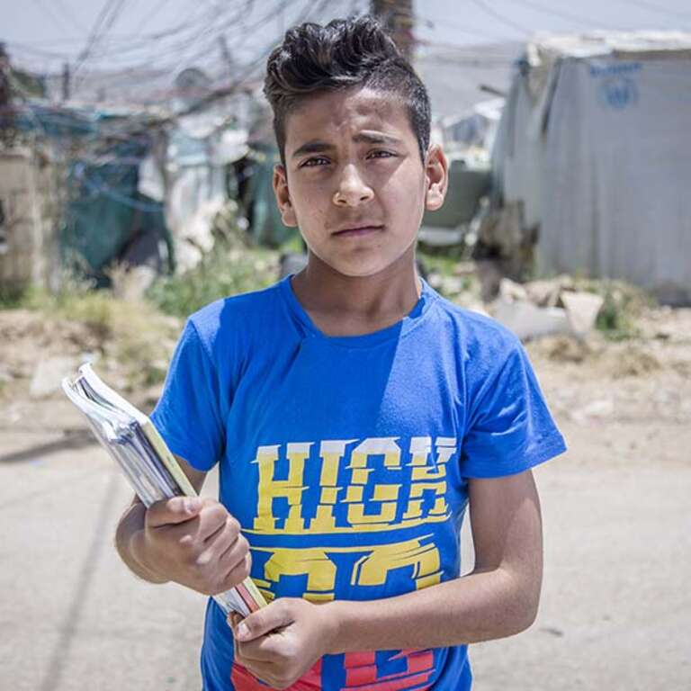 Siraj, age 13, looks concerned, as he stands in the informal, tented settlement where he lives, holding some notebooks.