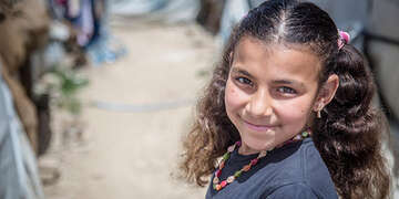 An 11-year old girl smiles while standing in an informal tented settlement in the Bekaa Valley, Lebanon.