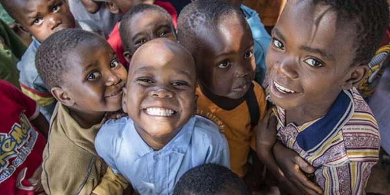 A group of school children crowd together towards the camera and smile while attending a Save the Children supported preschool in Malawi.