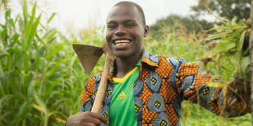 A Youth in Action program graduate student named Kassoum proudly stands in a field in Burkina Faso that is brimming with large, green crops. As the sun shines, Kassoum holds a large harvesting tool over his shoulder and smiles as he displays the freshly picked vegetables his year-round small farm produces. In partnership with Mastercard Foundation, Save the Children's Youth in Action program works to improve the socio-economic status of over 40,000 out-of-school youth, girls and boys, aged 12-18 in rural Burkina Faso, Egypt, Ethiopia, Malawi and Uganda. Photo credit: Harrison Thane | Save the Children, August, 2017.