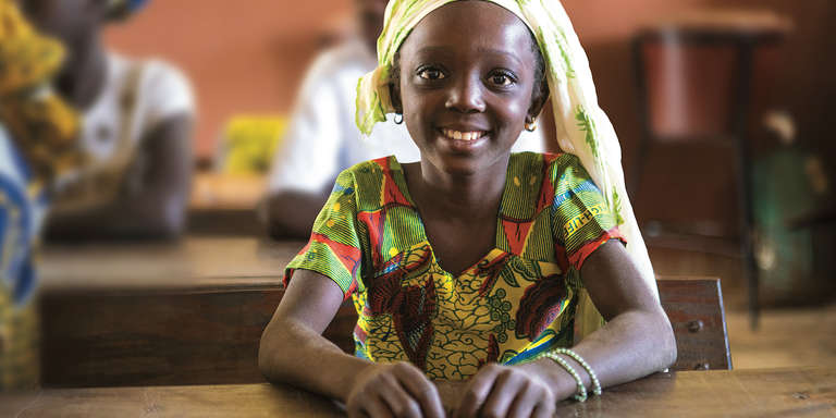 A smiling young girl sits in her classroom in Mali. Talitha Brauer 2017.