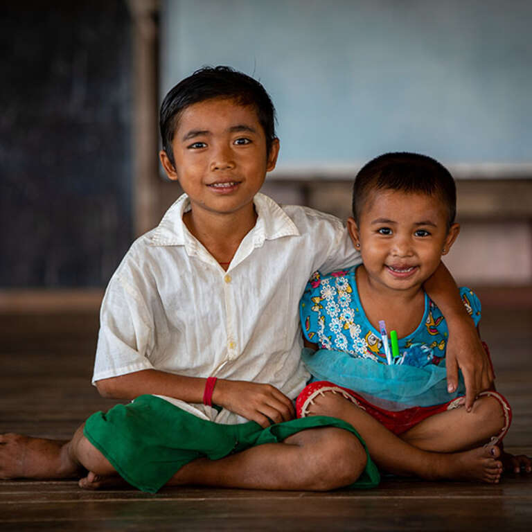 A 10-year-old boy rests with his arm around his little sister's shoulder. The siblings are seated in a classroom in Myanmar, where they live in a community that struggles with educational resources. Photo credit: Victoria Zegler / Save the Children, April 2018.