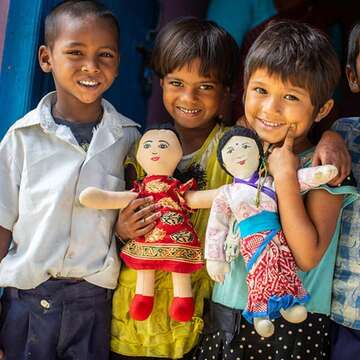 A group of smiling children stand together outside their early learning center in Saptari, Nepal.