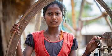 Mamta, age 10, wearing a simple red and blue dress and a serious expression, stands outside her family home in Nepal, worrying about child marriage.