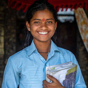 16-year-old Sonu holds onto her school textbook inside of her home in the Kapilvastu region of Nepal.