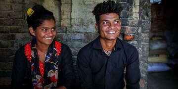 16-year-old Sonu, left, sits beside her 19-year-old brother Ganesh inside of her family home on within the Kapilvastu region of Nepal.