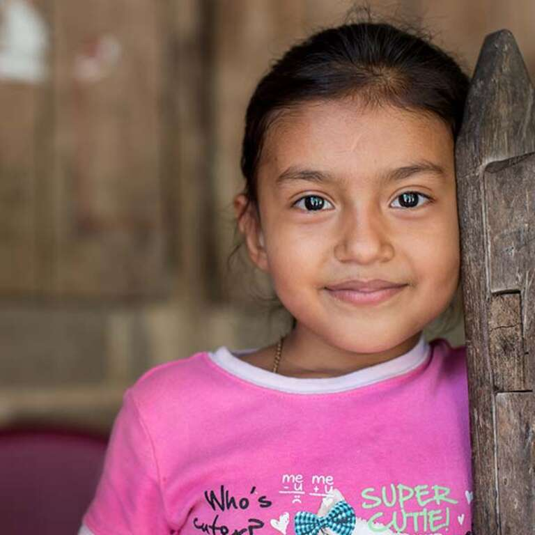 Six-year-old Manela, wearing a pink shirt, smiles as she leans against a wooden door.