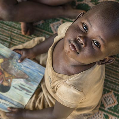 A child at a reading workshop run by Save the Children at Mahama Refugee Camp, Rwanda