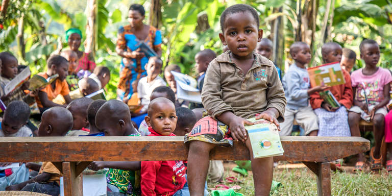 A group of children sit on benches outside on a sunny day in Rwanda. One child sits on a bench and holds a picture book while several others sit on the grass behind him with their eyes focused on the books in their hands. The children are practicing their reading at Save the Children's reading club in their community. Photo credit: Jonathan Hyams / Save the Children, Dec 2017.