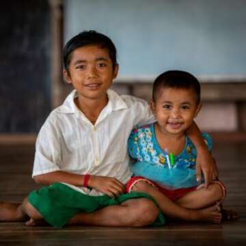 Two siblings smile while sitting on the floor of their Save the Children-supported school classroom in Myanmar. Donating to charity can help children in need.