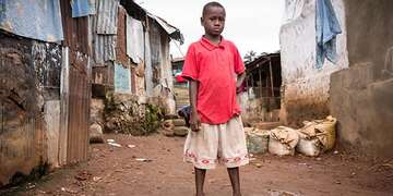 An 11-year old boy stands near his home in the slum of Kroo Bay, Sierra Leone
