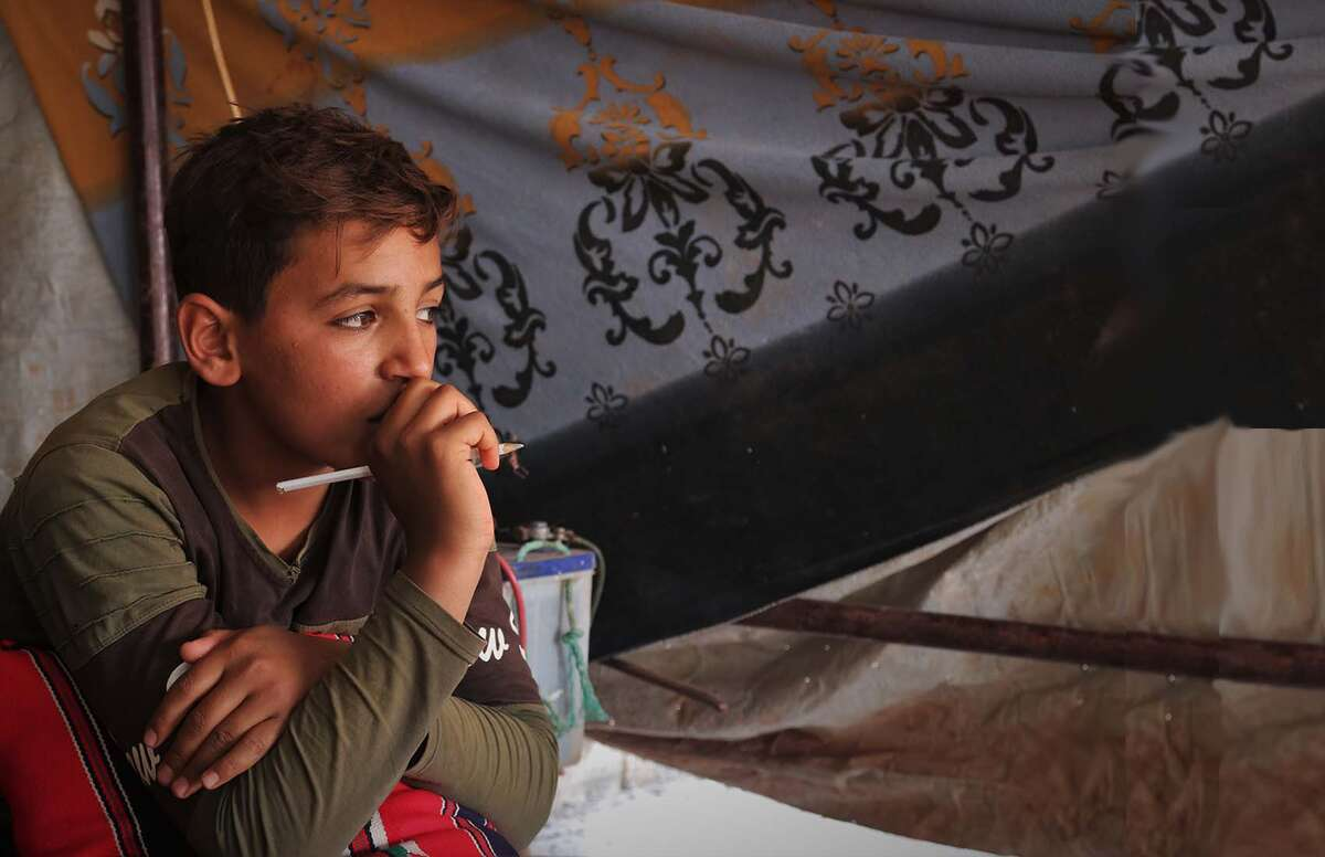 A 12-year old boy uses a cell phone to continue studying outside of school while resting at his home in a refugee camp in Syria.