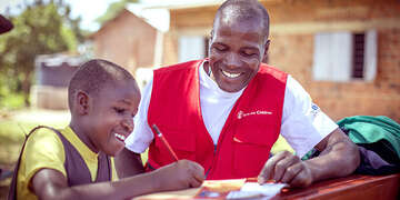 Fred, a Save the Children staff member, guides Dorothy on how to write a letter.