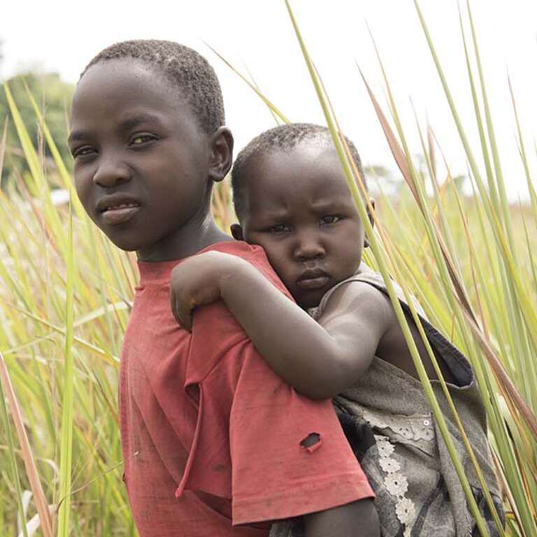 A young girl carries her baby sister on her back in the land surrounding the family home in Kaseses, Uganda
