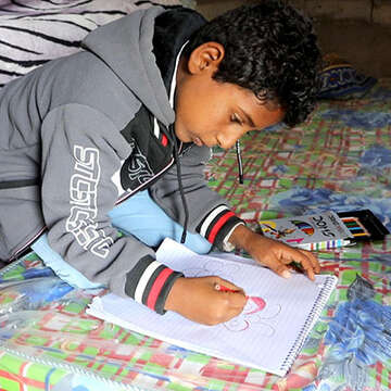 Ali* drawing a picture. He and his family fled fighting in Sana'a in Yemen.