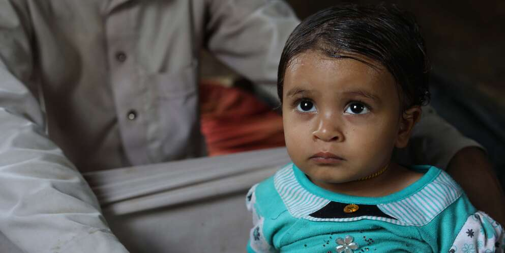 A baby girl sits near her father in Yemen where she is receiving medical treatment for malnutrition.