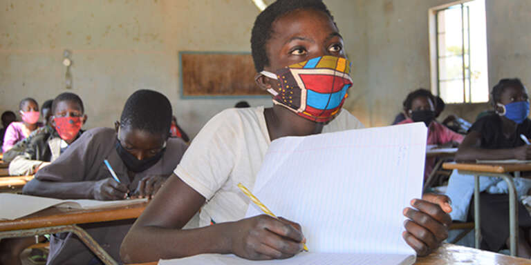 A girl wearing a face mask takes an exam in her classroom in Zambia where schools have reopened since being closed since March due to COVID-19.