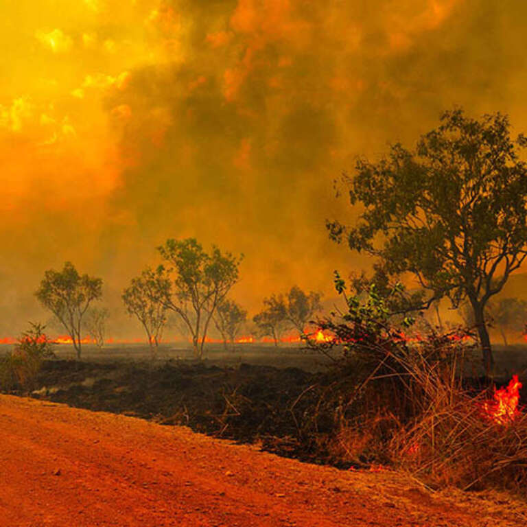 An empty dirt road reflects the red blaze of the enormous and unprecedented Australian bush fires. Smoke and flames appear in the distance, while parts of the horizon are actively burning. Save the Children is helping children and families in Australia who have been impacted by the fires. Photo credit: John Crux Photography.