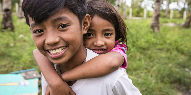 Gerald, 12, smiles widely while giving his younger sister, six, a piggyback ride at their home in the Philippines. The siblings were impacted by a devastating typhoon and received support from Save the Children. Children are escpecailly vulernable in the wake of natural disasters, as they my be left alone, without food or shelter, and unable to return to school. Sponsorship programs in the Philippines support children like Gerald and his younger sister so that they may thrive and be better prepared for the future. Photo credit: Jonathan Hyams / Save the Children, March 2017.