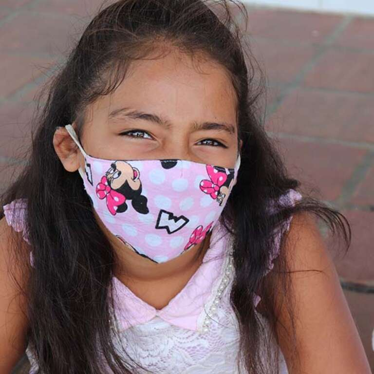 A girl wears a Minnie Mouse mask.