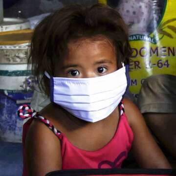 A young girl wears a cloth face mask to protect herself from coronavirus.