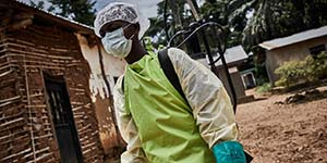 A staff member wears a mask and gown to protect themselves from Ebola.