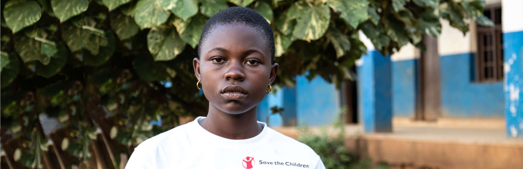 "A 13-year old girl named Stephanie wears a white Save the Children t-shirt with the word ""Ebola"" printed on it. She is standing outside of a blue building. Stephanie lives in North Kivu and has attended one of Save the Children's Ebola awareness classes where she learnt how to protect herself from the disease. North Kivu has experienced years of conflict and is currently the site of the world's second largest Ebola virus disease outbreak. Photo credit: Sacha Myers/Save the Children; Feb 2019."