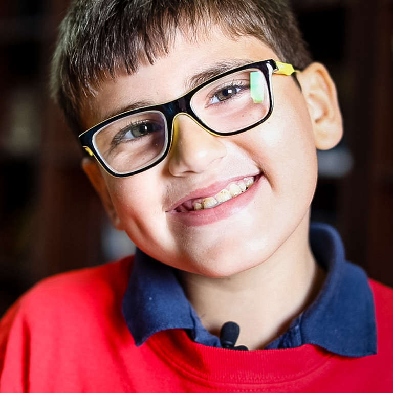 11-year old Karim* wears a pair of glasses and a red t-shirt and smiles broadly. Karim and his family are Syrian refugees who fled their country in 2012 in hopes of a better life. Thanks to Save the Children's refugee sponsorship program, children like Karim are benefitting from protection, education, health and livelihoods support, counseling and psychological support. Photo credit: Victoria Zegler | Save the Children, Nov 2017. *Name changed for protection.