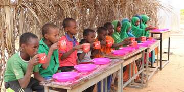 A group of children enjoys a nutritious meal supplied by Save the Children at an elementary school in the Somali Region of Ethiopia. Photo credit: Seifu Assegid / Save the Children, July 2019.