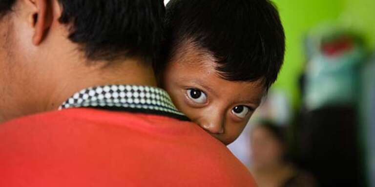 3-year-old Esbin peeks at us over his father's shoulder in an emergency shelter.