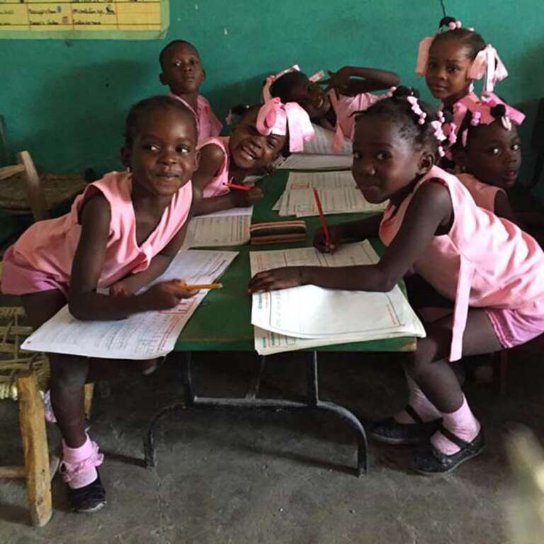 Young schoolchildren in Haiti, dressed in pink uniforms, are busy with their lessons.