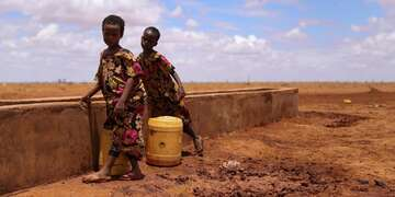 Two boys stand with a bucket in a drought-affected area in the Horn of Africa