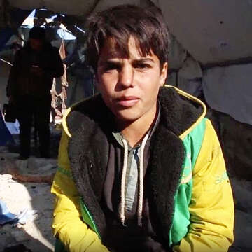 A 13-year old boy who lives in the Idlib, Syria camp that was hit by a missile attack on November 20, 2019 sits amid the chaos and aftermath of the bombing, In the background, people look through the rubble. Photo: Save the Children, November 2019.