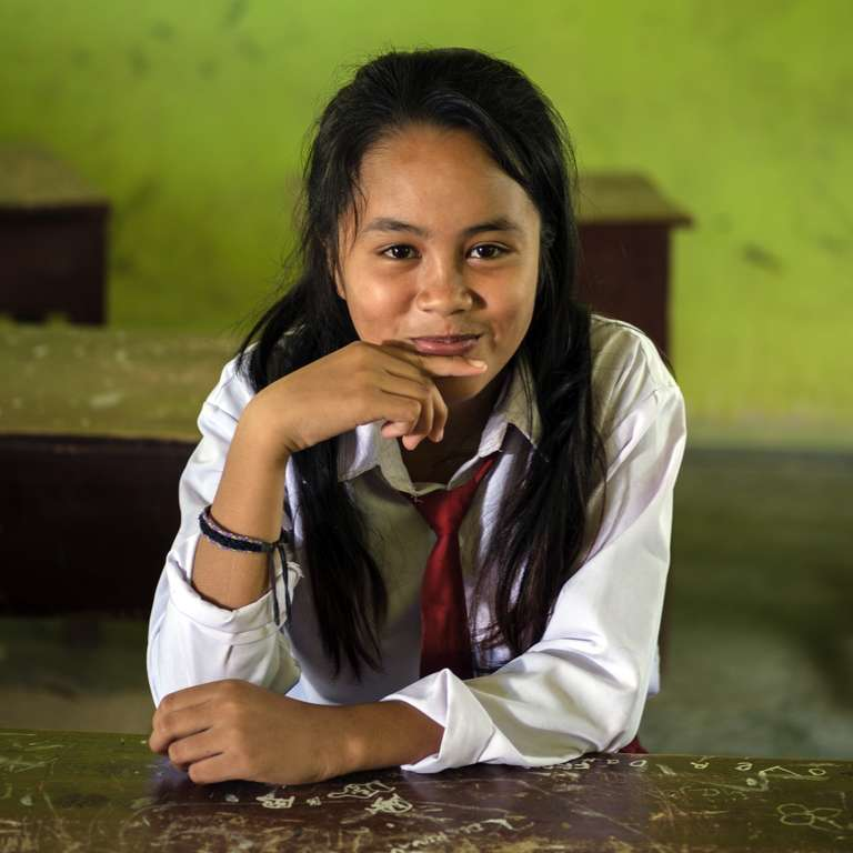 12-year old Marzela smiles while sitting at a desk in her elementary school Central Sulawesi, Indonesia. Marzela lost her home during the deadly 2018 Indonesia earthquake and tsunami. Her family received a multi-purpose grant from Save the Children to rebuild their lives. Photo credit: Jiro Ose / Save the Children, Feb 2019