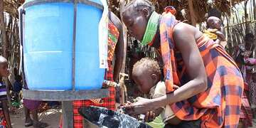A woman and her child use a hand-washing station in Northern Kenya.